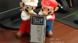 Mario and Fire Mario posing next to their new portable home.
